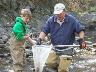 Toby Smith fishes in a stream with club member Ben Werchowsky
