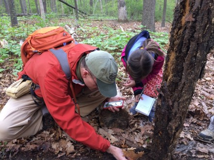 Photo of John and Josie Buchanan examining a salmander on a hike in Barcroft Park