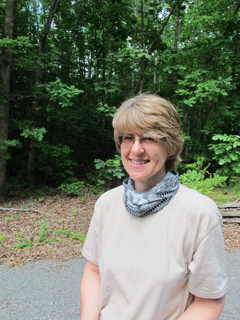 Photo of ARMN member Susan Berry wearing a blue bandanna standing in front of the woods