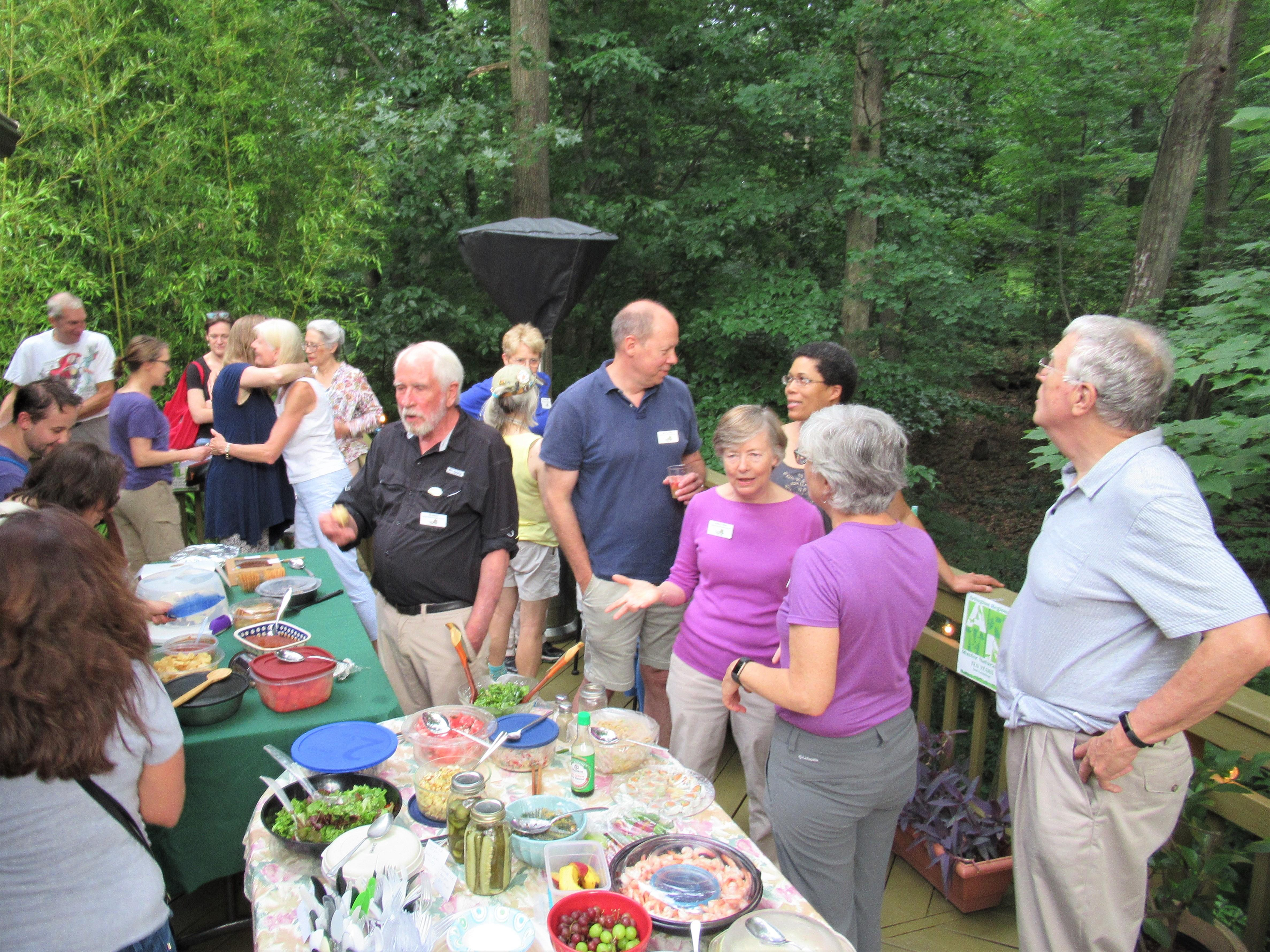 Photo of ARMN members standing around tables at a potluck