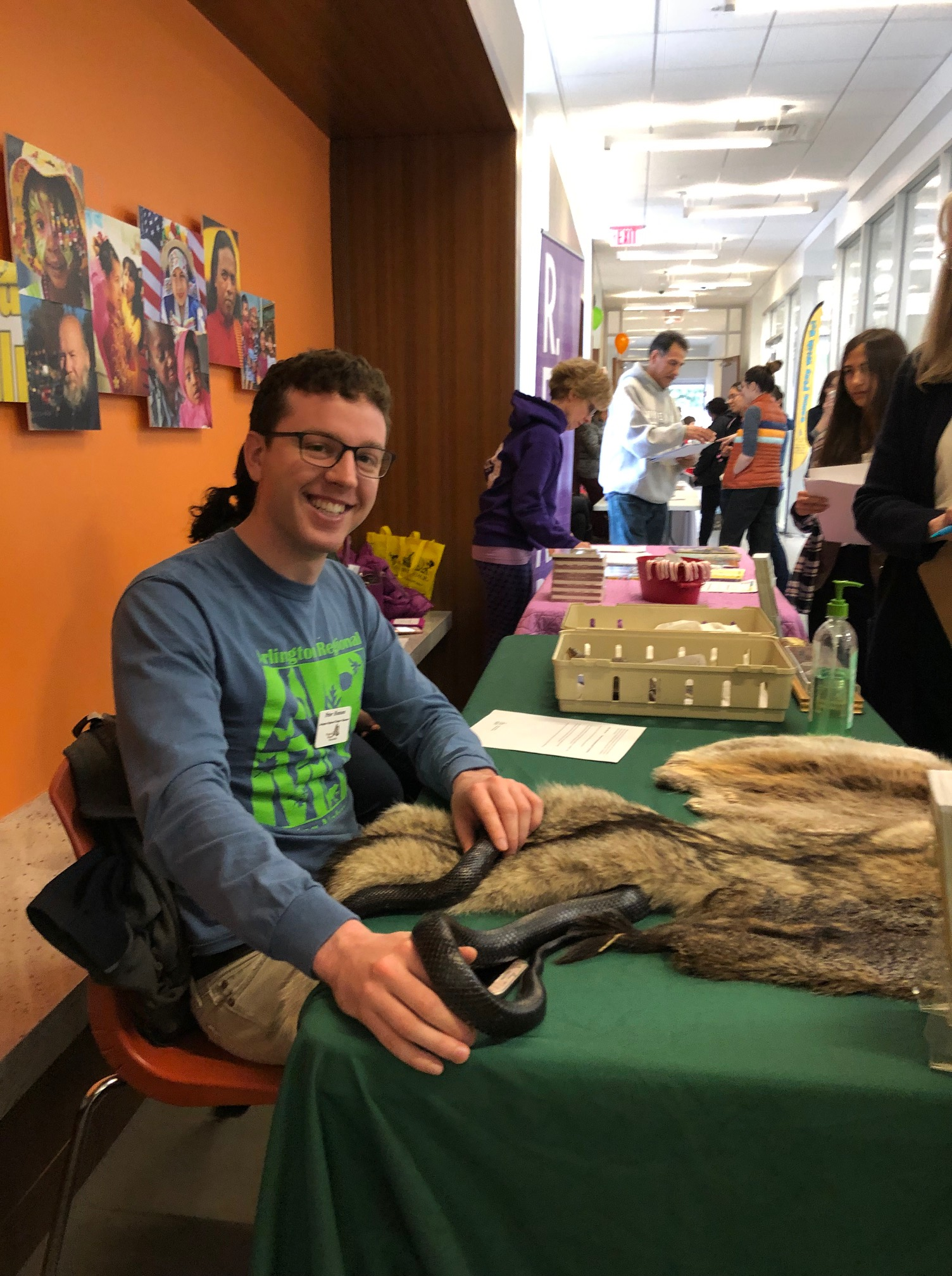 ARMN volunteer Peter sitting at a table holding a black snake while other volunteers stand behind him.