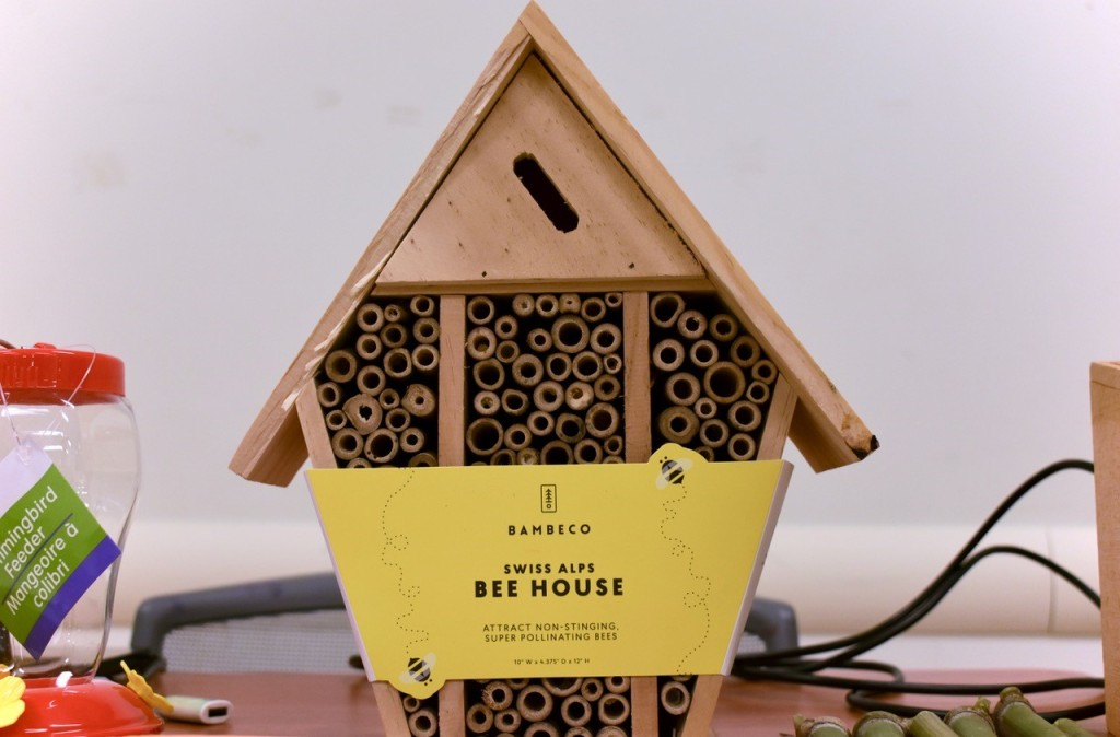 "Photo of a ""bee hotel,"" which shaped like a bird house but filled with cut bamboo"
