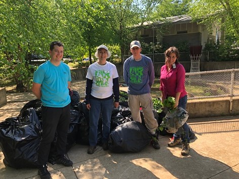 Photo of four people standing in front of bags filled with pulled invasive vegetation