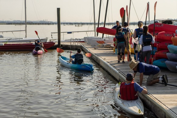 People launch kayaks from a wooden dock