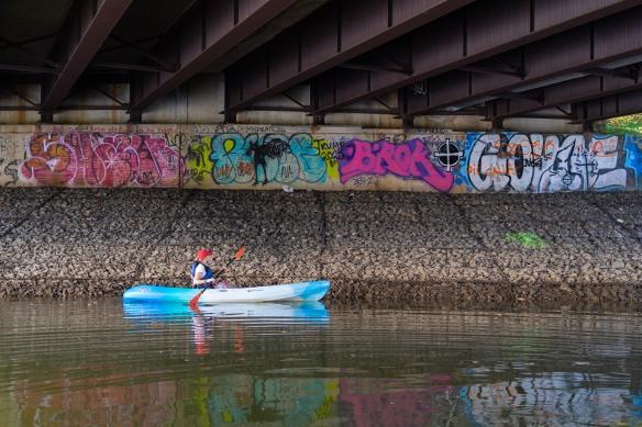 A kayaker paddles beneath a bridge covered in graffiti