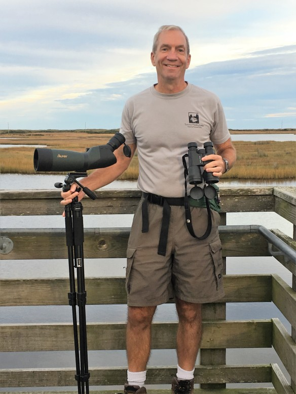 ARMN volunteer Phil poses in front of a marsh with two sets of binoculars