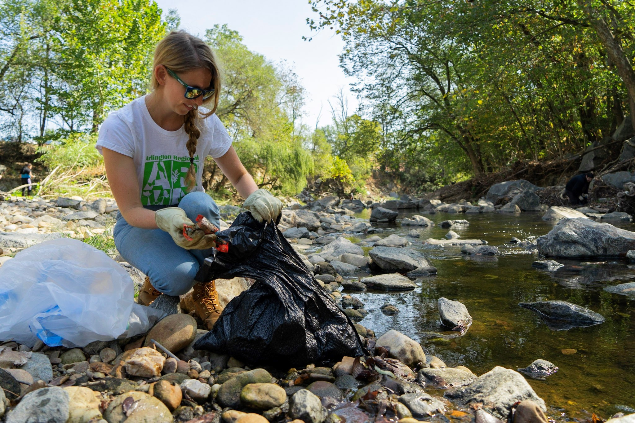 A woman kneels next to a stream putting trash into a trash bag.