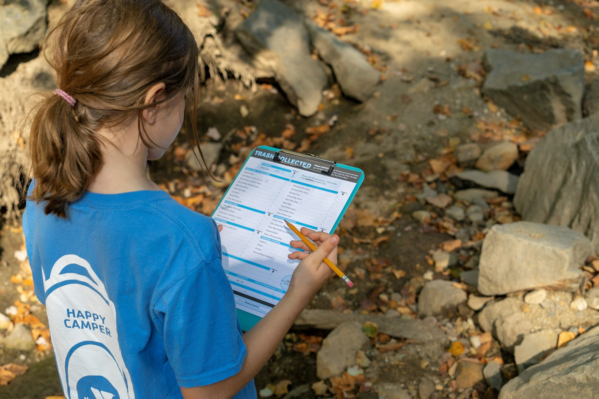 A girl holds a pencil and consults a checklist by the stream.