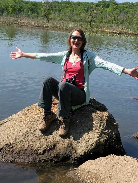 Photo of Beth Kiser sitting on a rock in water