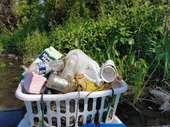 Photo of a bin filled with trash from the creek
