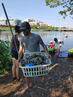 Photo of a volunteer carrying a bin of trash from the creek