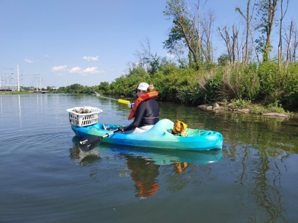 Photo of a volunteer picking up litter while in a kayak