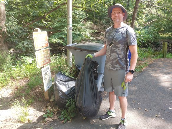 Photo of a volunteer standing next to trash bags